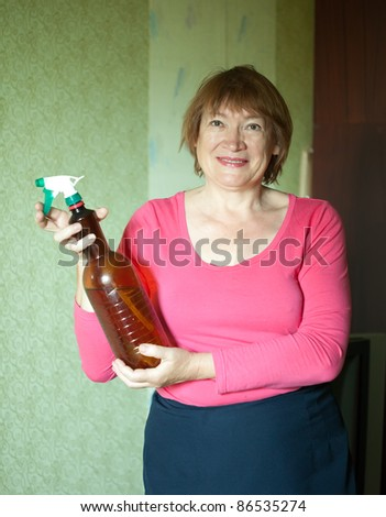 Mature woman with spraying bottle in home