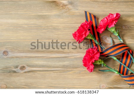 9 May background - red carnations and George ribbon on the wooden background, free space for text #618138347