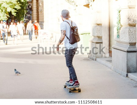13 MAY 2018, BUDAPEST, HUNGARY: Man riding on a skateboard at the city street #1112508611