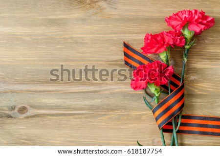 9 May card - red carnations and George ribbon lying on the wooden background with free space for text #618187754