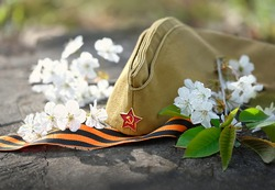 9 may holiday, Victory Day background. George ribbon, old military cap and spring flowers. symbol of 9 may, memory of war 1945.