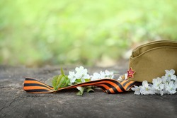 9 may holiday, Victory Day background. George ribbon, old military cap and spring flowers. symbol of 9 may, memory of war 1945. copy space