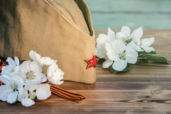 9 may, holiday Victory Day. George ribbon, spring flowers and military cap. copy space