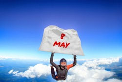 8 May. Parachutist flies a flag with date of May 8. Skydiver in black suit. Extreme as a way of life.