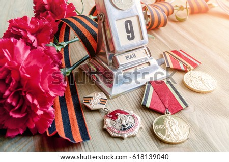 9 May Victory Day holiday still life - vintage metal desk calendar with 9 May date, medals, George ribbon, red carnations bouquet - 9 May concept. Selective focus at the calendar #618139040