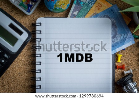 1MDB inscription written on book with globe,eyeglasses, calculator, camera, pencil and vase on wooden background with selective focus and crop fragment. Business and education concept Stock fotó ©