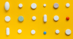 Medical white pills on a yellow background. Pharmaceutical concept