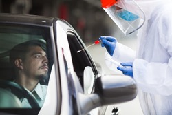 Medical worker performing drive-thru COVID-19 test, taking nasal swab specimen sample from male patient through car window, PCR diagnostic for Coronavirus presence