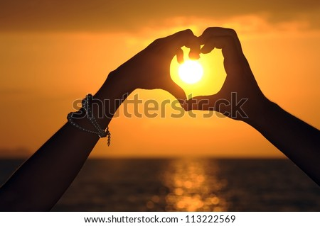 Men and women made ??a heart shape. heart shape made with the couple's hands at sunset