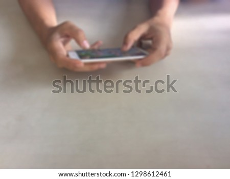 Men play games in the smartphone for a long time, blurred. #1298612461