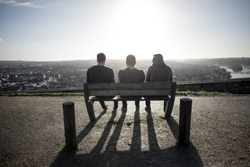 3 men unrecognizable sitting and relaxing on a bench in the sun enjoying a city scape view