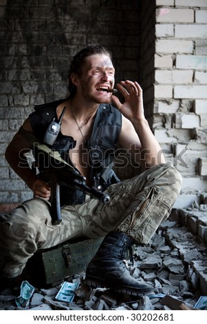 Mercenary with 'Kalashnikov' submachine gun and big cigar is sitting