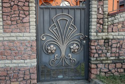 metal closed door with a  forged pattern and a part of a stone wall of a fence on the street