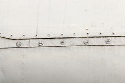 metal surface of old unused airplane gray. In paint, some visible damage, as well as metal rivets and bolts connecting the sheets of material. Small depth of field.