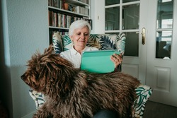 Middle-aged woman with white hair making a video call with her tablet accompanied by her loving dog. Social distancing due to covid19. Stay Home