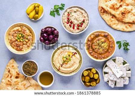 Middle eastern, arabic traditional breakfast with hummus, foul, mutabbal, qudsia and zaatar. Top view	                               Stockfoto ©