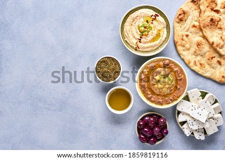 Middle eastern, arabic traditional breakfast with hummus, foul, white cheese and zaatar. Top view  with copy space