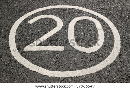 20 miles per hour sign on a tarmac road.