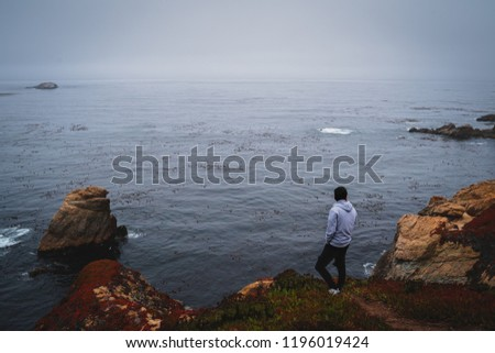 millennial man male guy being introspective along the coastline past Monterey California and Carmel by the sea in a foggy and serene peace by the ocean thinking about what is next and existence