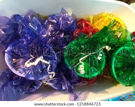 Mishloach manot wrapped in colored paper Delivery of candy wrapped in colored paperBowls Packed with cellophane in a transparent blue, transparent green and yellow  #1258846723