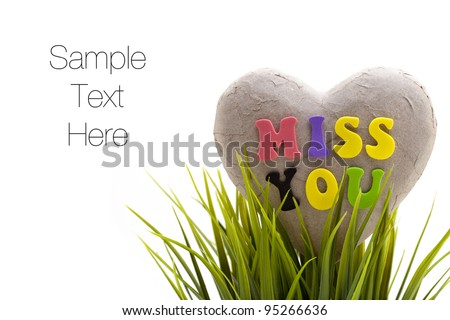 'Miss you' sentiment spelled out with letters on broken heart made of paper, isolated on white background