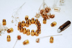 1ml amber glass vials arranged in love heart shape with dried flowers and roller bottles. Natural health and wellness background image.