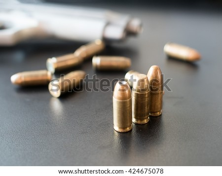 11mm bullets and short gun on black background. (selective focus)