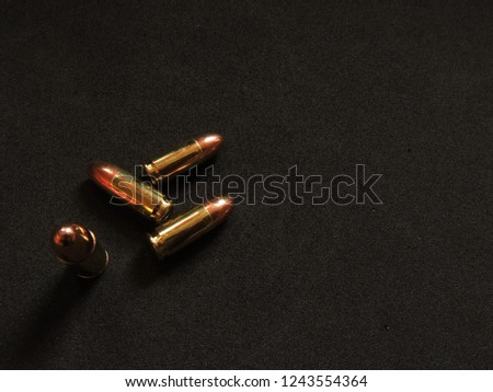 9mm copper ball ammo with brass shell on charcoal grey background  #1243554364