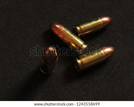 9mm copper ball ammo with brass shell on charcoal grey background #1243558699