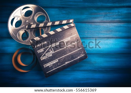 35mm film, reel and movie clapper with dramatic lighting on a wooden background