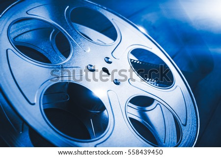 35 mm film reel with dramatic lighting and lens flares on a wooden background