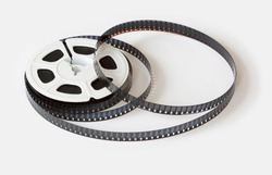 8mm film reel with film strips scattered around. Studio shot, Close-up image isolated on white background.