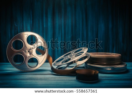 35 mm film reels and cans with dramatic lighting on a wooden background