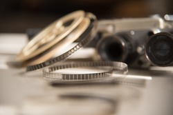 8mm film strip against the background of an old movie camera in brown tones. Watching a movie
