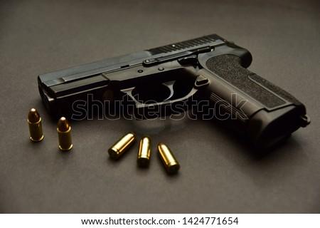 9mm gun and bullet on black background. Pistol isolated on black background. Hand gun and bullets on black background