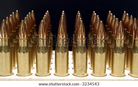 5.56mm .223 M16 AR15 rifle bullets vertical fading into background