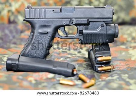 9mm military sidearm with a tactical laser/light-module on camouflage