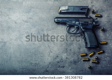 9 mm pistol gun and bullets strewn on the table.