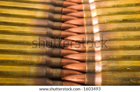 5.56mm rifle bullets in stripper clips laid tip to tip, with noses interlocking. Closeup.