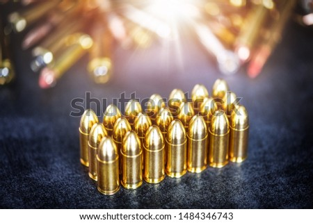 9mm rounds or bullets ammonution on dark stone table. Bullet pile in color background. Magazines, round and ammo military war technology. #1484346743