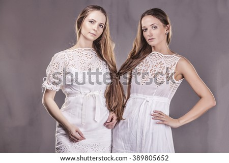Models beautiful women girlfriends in soft dresses with long hair affectionately communicate with each other #389805652
