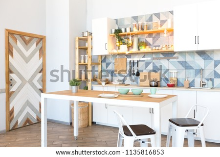 modern bright and cozy kitchen in a studio apartment with decorated wall and door #1135816853