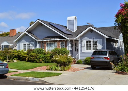 Modern house with garden, chimney and solar panels on the gable roof. LA, CA .
