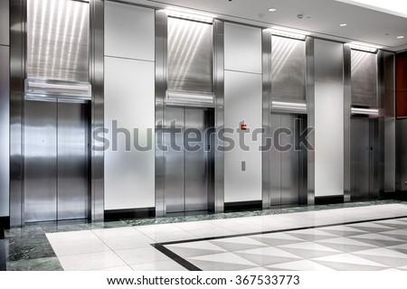 modern steel elevator cabins in a business lobby