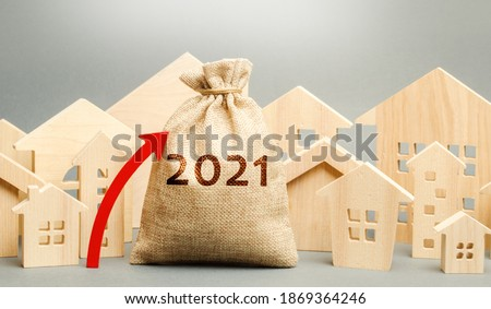 2021 money bag with up arrow and miniature houses. Real estate planning and financing concept. Housing market. Mortgage, loan, investment. Repairs and refinance home. Investing in construction