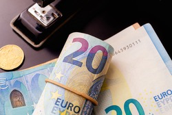 Money, EURO - EUR. Euro banknotes on a dark colored table. Highlight for the 20 Euro note on a roll of money with rubber alloy. Photo with a view from above. A stapler and golden coin in composition.