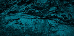 Monochrome dark turquoise toned rock texture. Weathered crumbling mountain surface. Close-up. Combinations of teal color and rough stone surfaces. Blue rocky stone background.