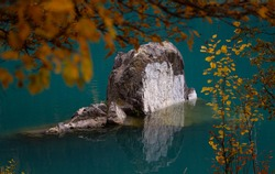 Monolithic stone standing in water, framed by trees in autumn color