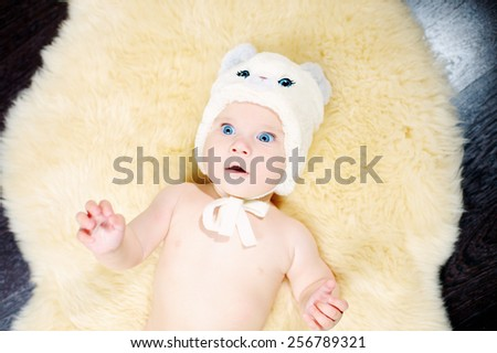 6 month blue-eyed baby in beige hat with blue eyes and ears on a beige fur on the floor