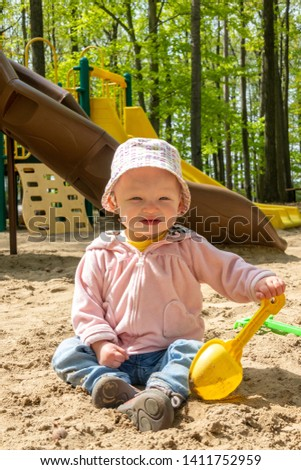 15 month old adorable blond caucasian toddler playing on sand box at the public park outdoor Sorel-Tracy Quebec Canada playing on sand box at the public park outdoor Sorel-Tracy Quebec Canada #1411752959